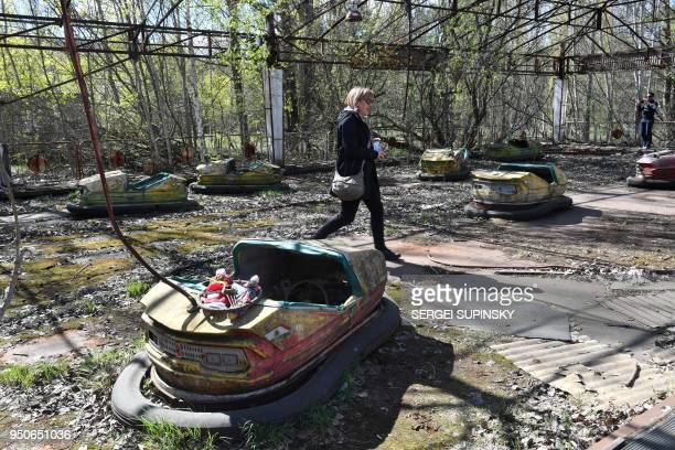 Tourist walk in an abandoned park of the ghost city of Pripyat located near Chernobyl Nuclear power plant during their tour to the Chernobyl...