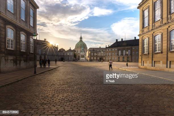 tourist walk into amalienborg palace, copenhagen, denmark, at the sunset time - palazzo reale foto e immagini stock