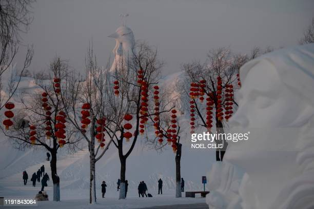 Tourist walk past ice sculpture during the Harbin International Ice and Snow Festival in Harbin in China's northeast Heilongjiang province on January...