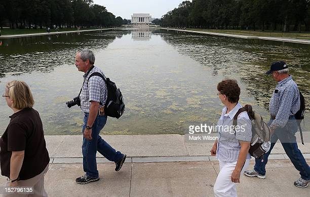 Tourist walk past the Reflecting Pool in front of the Lincoln Memorial that is full of algae after recently being filled with water on September 26...