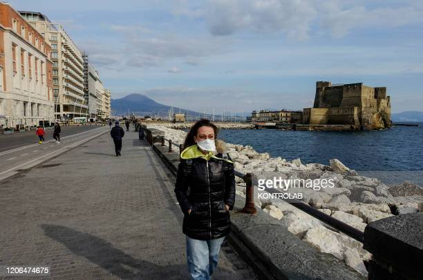 Tourist walk through a deserted Caracciolo street in Naples, while Italy imposed unprecedented national restrictions on its 60 million people on...