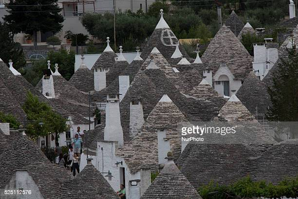 Tourist walk through Alberobello's streets on Aug 5 2014 Alberobello is a town in south east part of Italy in the Bari province with its unique...