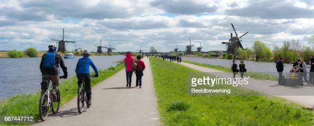 Tourist walking  and cycling past the windmills of Kinderdijk