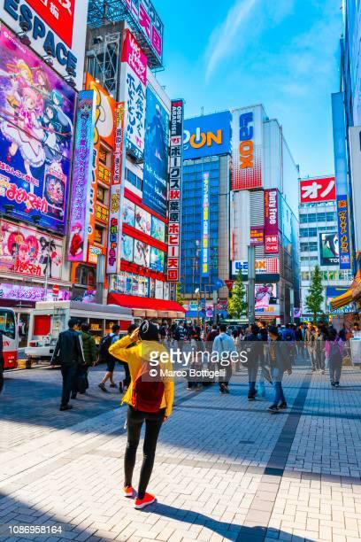 tourist walking in akihabara electronic town, tokyo, japan - akihabara stock pictures, royalty-free photos & images
