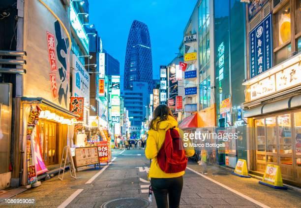 tourist walking in shinjuku at dusk, tokyo, japan - 観光 ストックフォトと画像