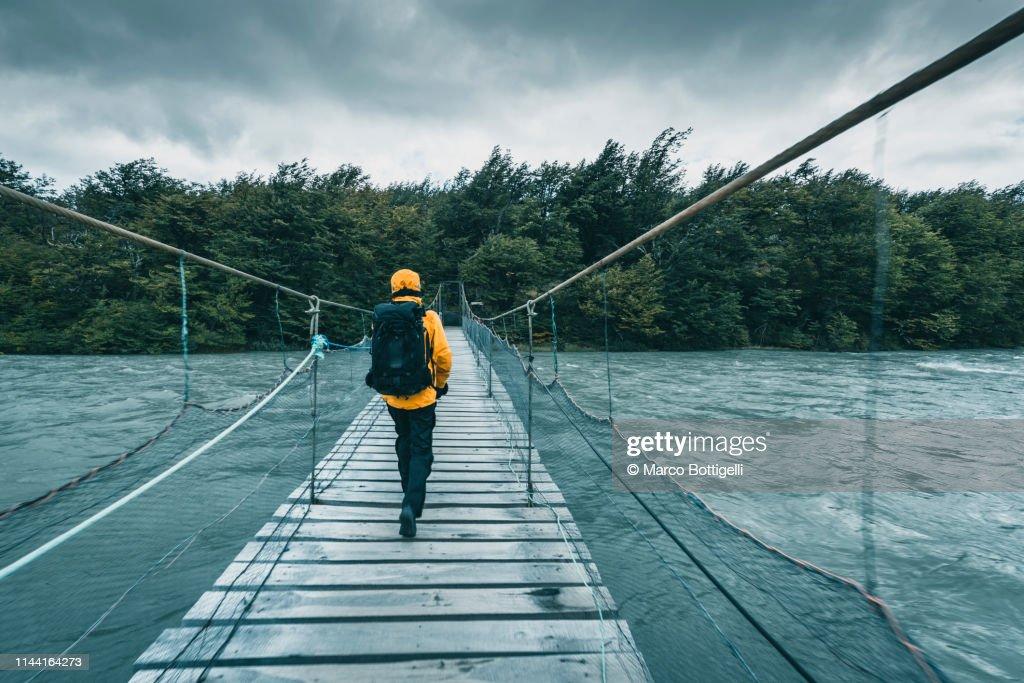 Tourist walking on a wooden bridge over a swollen river : Stock Photo
