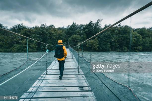 tourist walking on a wooden bridge over a swollen river - hängbro bildbanksfoton och bilder
