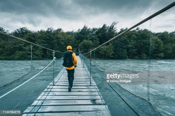 tourist walking on a wooden bridge over a swollen river - loopbrug stockfoto's en -beelden