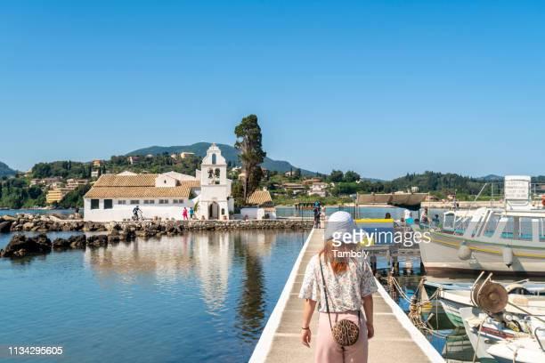tourist walking on bridge leading to vlacherna monastery, island on background, corfu, kerkira, greece - corfu stock pictures, royalty-free photos & images