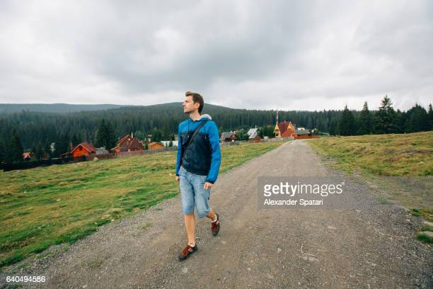 Tourist walking on the dirt road in rural area in Romania