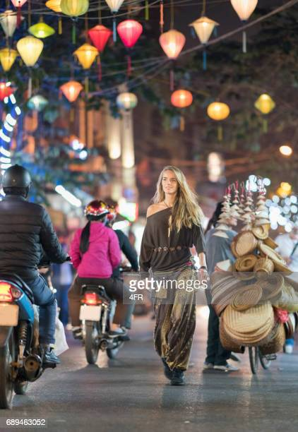 tourist walking through downtown old quarter hanoi at night, vietnam - vietnam stock pictures, royalty-free photos & images