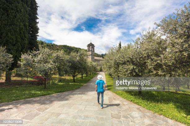 tourist walking to the old abbey, italy - abby road stock photos and pictures