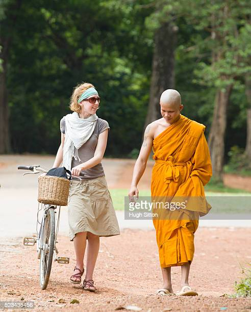 tourist walking with local monk, angkor wat, cambodia - hugh sitton stock pictures, royalty-free photos & images