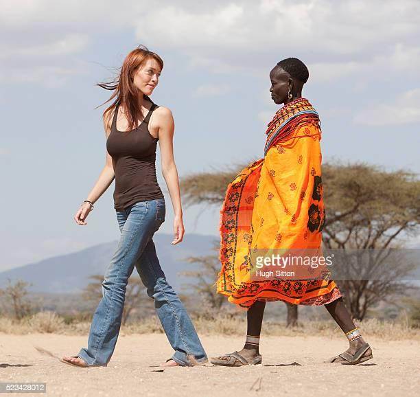 tourist walking with samburu tribeswoman in desert, kenya - hugh sitton bildbanksfoton och bilder