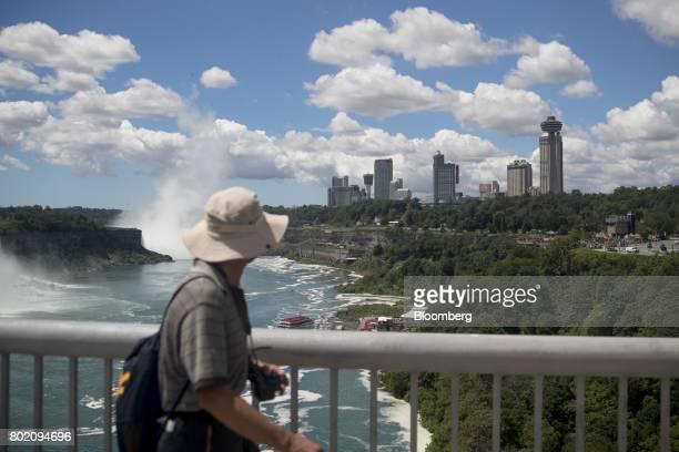 A tourist walks across the Niagara Falls International Rainbow Bridge in Niagara Falls Ontario Canada on Wednesday June 21 2017 The 150th anniversary...