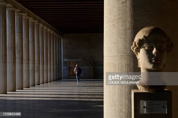 Tourist walks alone in an hallway of the Stoa of Attalos at the Ancient Agora, in Athens, on June 30 as the country opens up to tourism follwoing a...