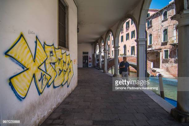 A tourist walks along the canal of Sant'Agostin where there are graffiti on the walls of the palaces on the way that connects St Mark square to the...