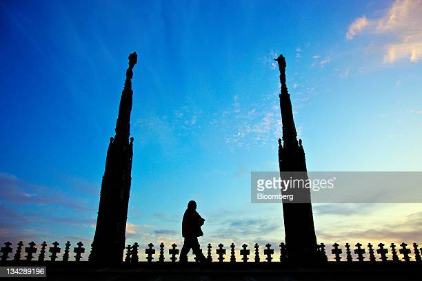 A tourist walks along the rooftop of Duomo di Milano or Milan Cathedral in Milan Italy on Tuesday Nov 29 2011 Italian Prime Minister Mario Monti said...