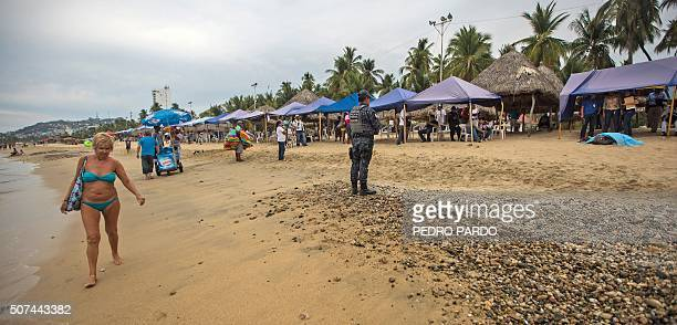 A tourist walks along the shore as forensic workers surround the body of a murdered man at Hornos beach in the tourist city of Acapulco Guerrero...