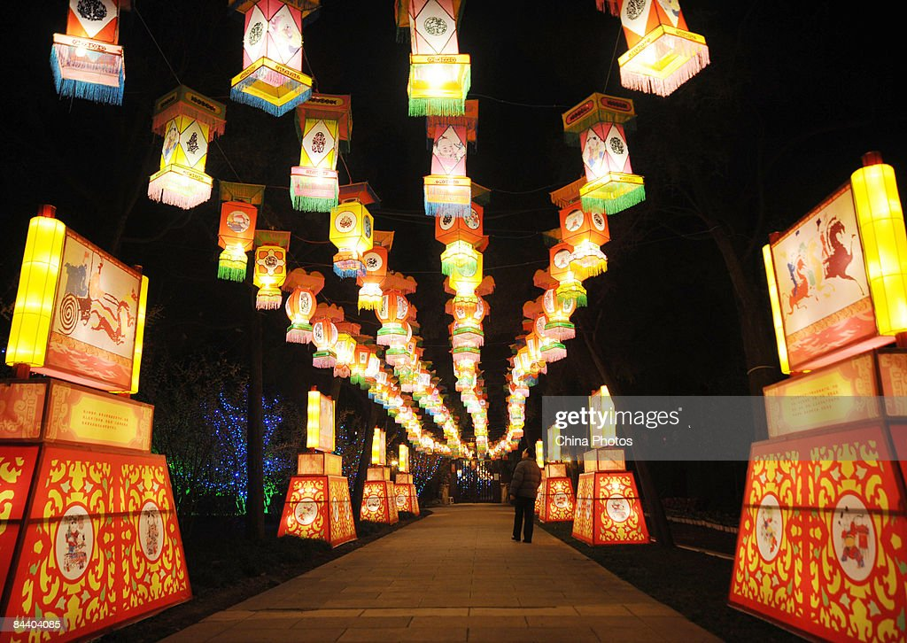 a tourist walks beneath holiday lanterns at the new year temple fair which will officially starts - Chinese New Year 2009