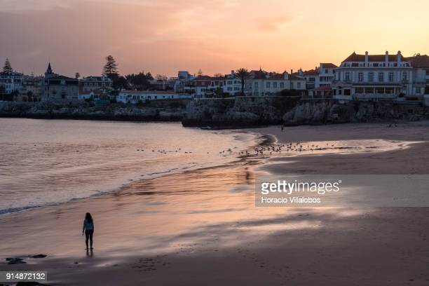 A tourist walks by the sea at sunset while enjoying mild winter weather at Praia da Duquesa on January 30 2018 in Cascais Portugal Mild and sunny...