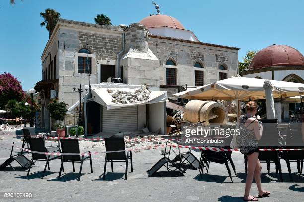 A tourist walks in front of a partially damaged mosque in the central square of the island of Kos on July 21 following a 65 magnitude earthquake...