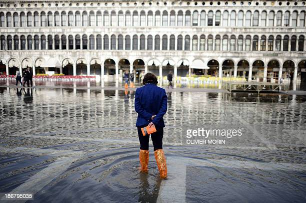 A tourist walks in the flooded Piazza San Marco on November 4 2013 in Venice Saint Mark's Square as the lowest point of Venice is always the first...