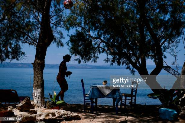 A tourist walks on a beach near the village of Skala Sykamineas in the northeastern island of Lesbos on August 3 2018