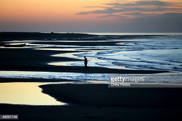 A tourist walks on a beach on July 5 2005 in Qinhuangdao of Hebei Province north China Qinhuangdao literally Qin Emperor's Island was named after an...