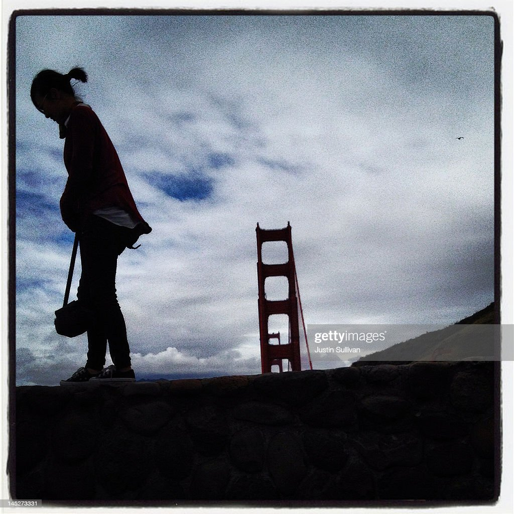 A tourist walks on a wall at a lookout point near the Golden Gate Bridge on May 3, 2012 in San Francisco, California. The Golden Gate Bridge, Highway and Transportation District is preparing for the 75th anniversary of the iconic Golden Gate Bridge that will be marked with a festival on May 26 - 27 that will feature music, displays of bridge artifacts and art exhibits. The 1.7 mile steel suspension bridge, one of the modern Wonders of the World, opened to traffic on May 27, 1937.