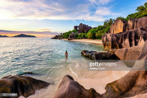 a tourist walks on anse source d'argent beach at sunset - majestic stock pictures, royalty-free photos & images