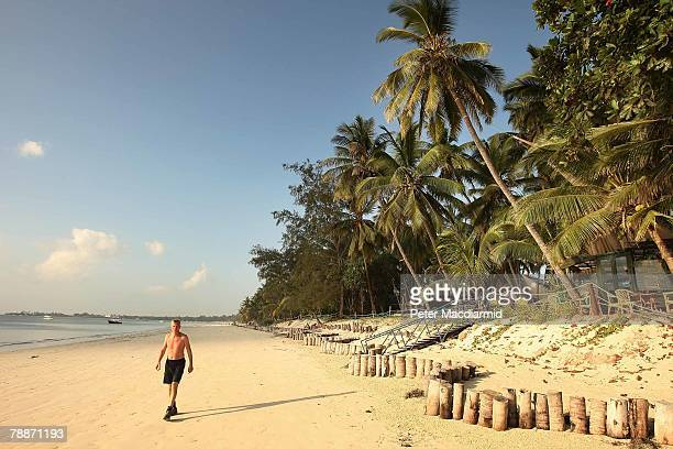 Tourist walks on the beach on January 10, 2008 in Mombasa, Kenya. Tourism is a $1 billion industry in Kenya. Some tour operators have temporarily...