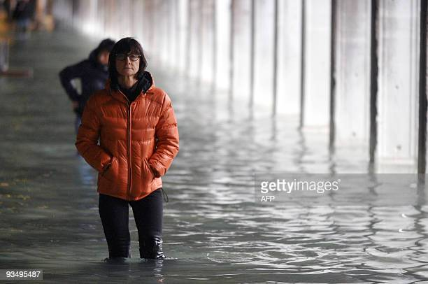 A tourist walks on the flooded Piazza San Marco on November 30 2009 in Venice The acqua alta a convergence of high tides and a strong sirocco stood...