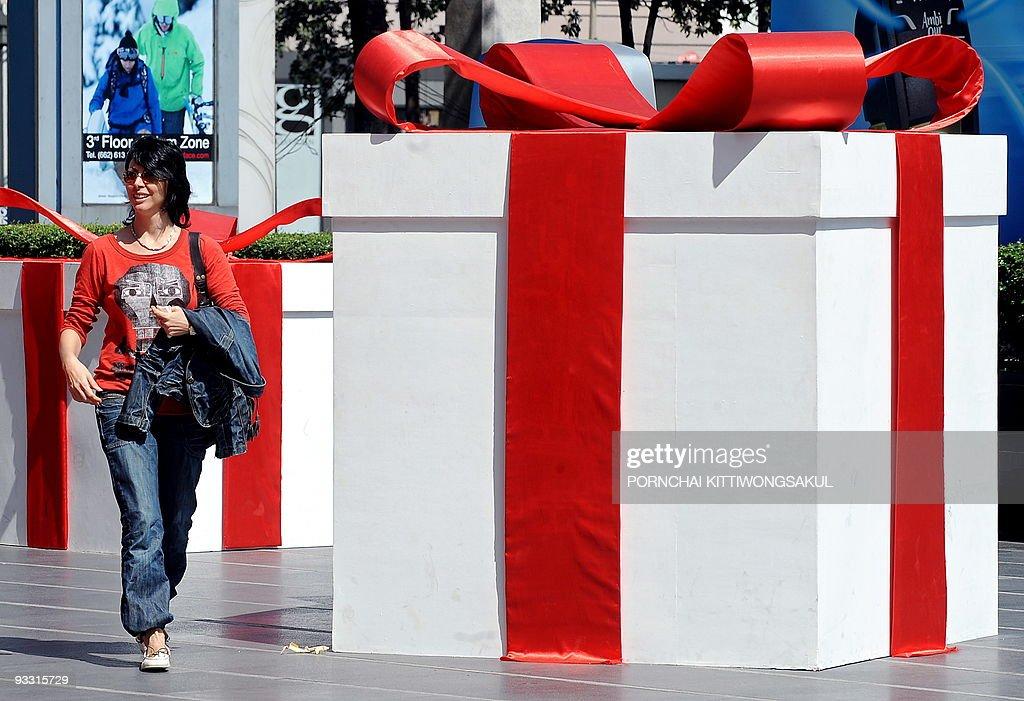 A tourist walks past a giant gift box di : News Photo