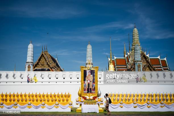 A tourist walks past a portrait of Thailand's King Maha Vajiralongkorn near the Grand Palace in Bangkok on May 3 ahead of the royal coronation which...