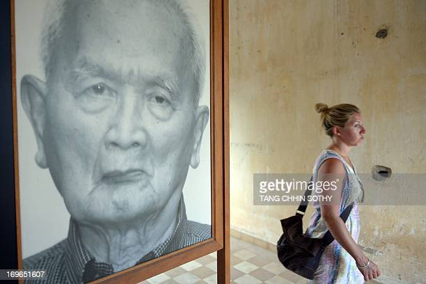 A tourist walks past a portrait photo of former Khmer Rouge leader 'Brother Number Two' Nuon Chea displayed for visitors at Tuol Sleng genocide...