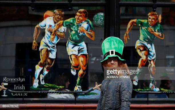 A tourist walks past Kennedys Pub with a rugby mural painted on the window following the St Patrick's Day in Dublin Ireland on March 17 2017 Ireland...
