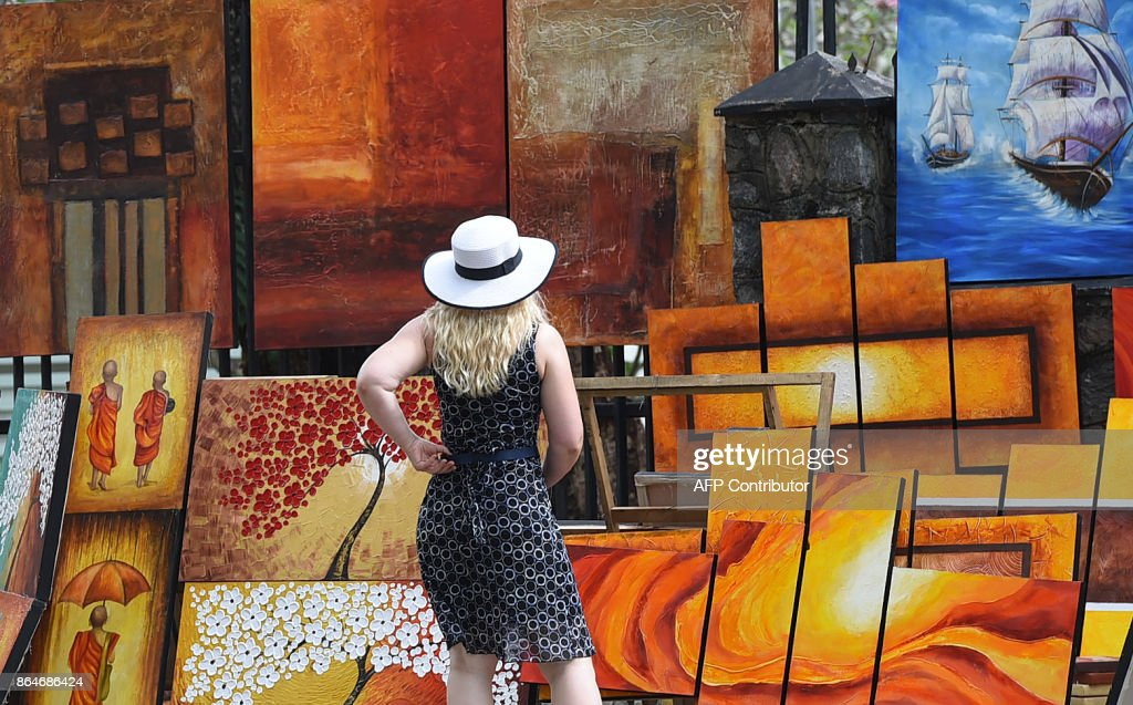 A tourist walks past paintings for sale on the roadside in the capital Colombo on October 21, 2017. /