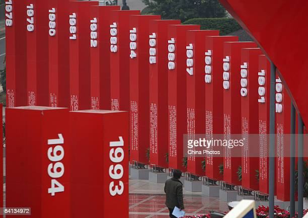 A tourist walks past pillars marked with years erected to mark the 30th anniversary of China's reform initiative at the People's Square on December...