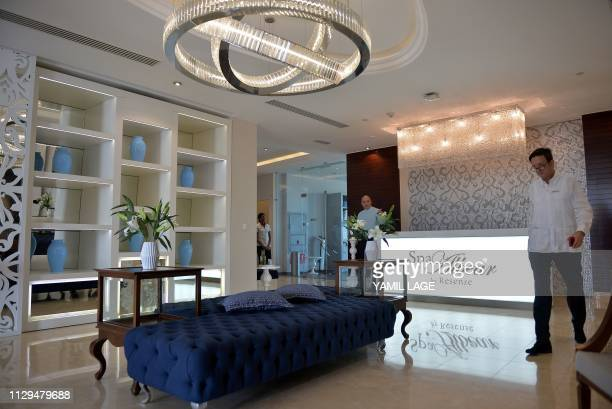 A tourist walks past the counter of the Spa Albear at the Gran Manzana Hotel in Havana on February 6 2019 Cuba attracts wealthy tourists with...