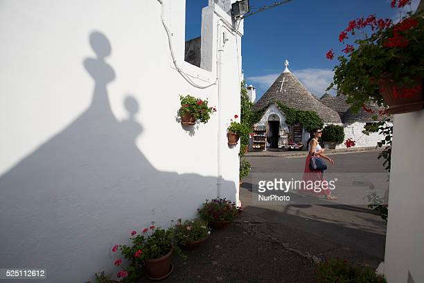Tourist walks through Alberobello's main street on Aug 5 2014 Alberobello is a town in south east part of Italy in the Bari province with its unique...