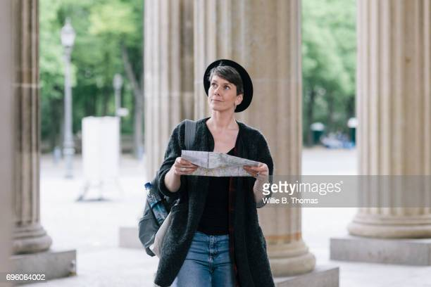 A Tourist Walks Through Historic Location Whilst Looking Over A Map
