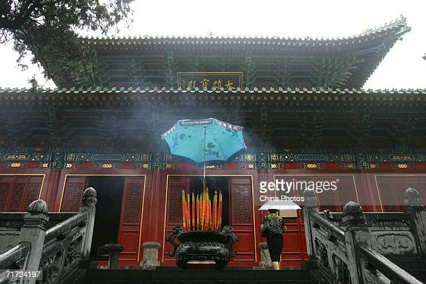A tourist walks to a shrine at Shaolin Temple on the Songshan Mountain on August 25 2006 in Dengfeng of Henan Province China Shaolin Temple built in...