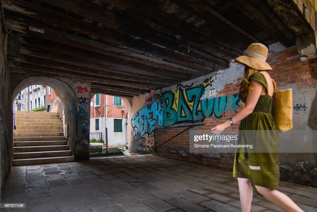 A tourist walks to cross the Anatomia bridge, where there are graffiti and tags on the walls, through Santa Croce district, on July 12, 2018 in Venice, Italy. The plague of graffiti and tags on the walls of the palaces of Venice continues with new writing across the doors, windows and the plaster of shops, banks, historic buildings, ruining and attacking the priceless architectural heritage of the lagoon. Venice has been living with this problem for years, but it has not reached a resolution until today.