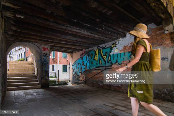 A tourist walks to cross the Anatomia bridge where there are graffiti and tags on the walls through Santa Croce district on July 12 2018 in Venice...