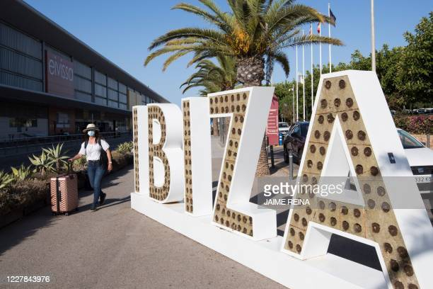 Tourist walks with her suitcase outside the airport in Ibiza on July 30, 2020. - With Spanish health authorities struggling with a rising number of...