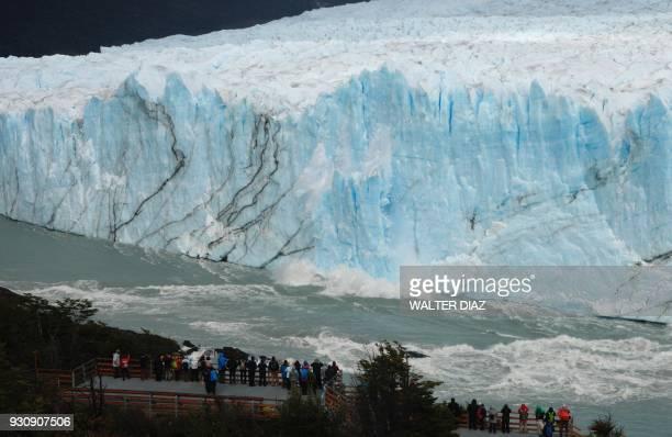 TOPSHOT Tourist watch pieces of ice falling from the Perito Moreno glacier at Parque Nacional Los Glaciares near El Calafate in the Argentine...