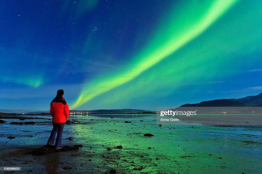 Tourist watches Aurora over fjord, Iceland : Stock Photo