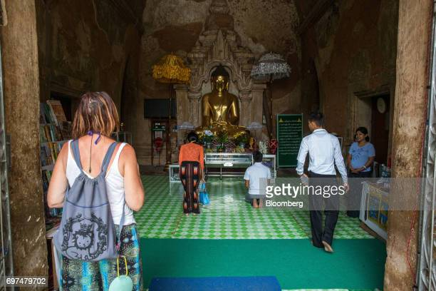 A tourist watches worshipers pray in front of a Buddha statue at a temple in Bagan Myanmar on Saturday June 10 2017 When the country opened to the...
