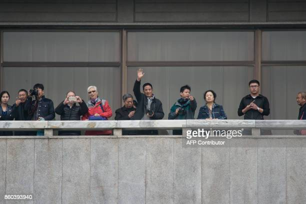A tourist waves from North Korea as he stands on a balcony of Panmon hall on the North side of the military demarcation line separating North and...